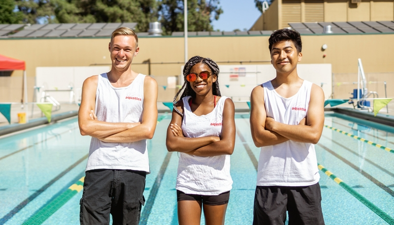 three student lifeguards standing in front of an outdoor pool